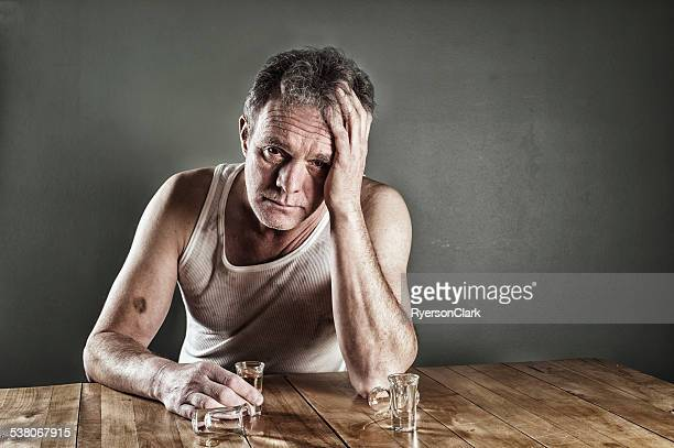 Alcoholism.  A Man Drinking at a Table, Drunk.