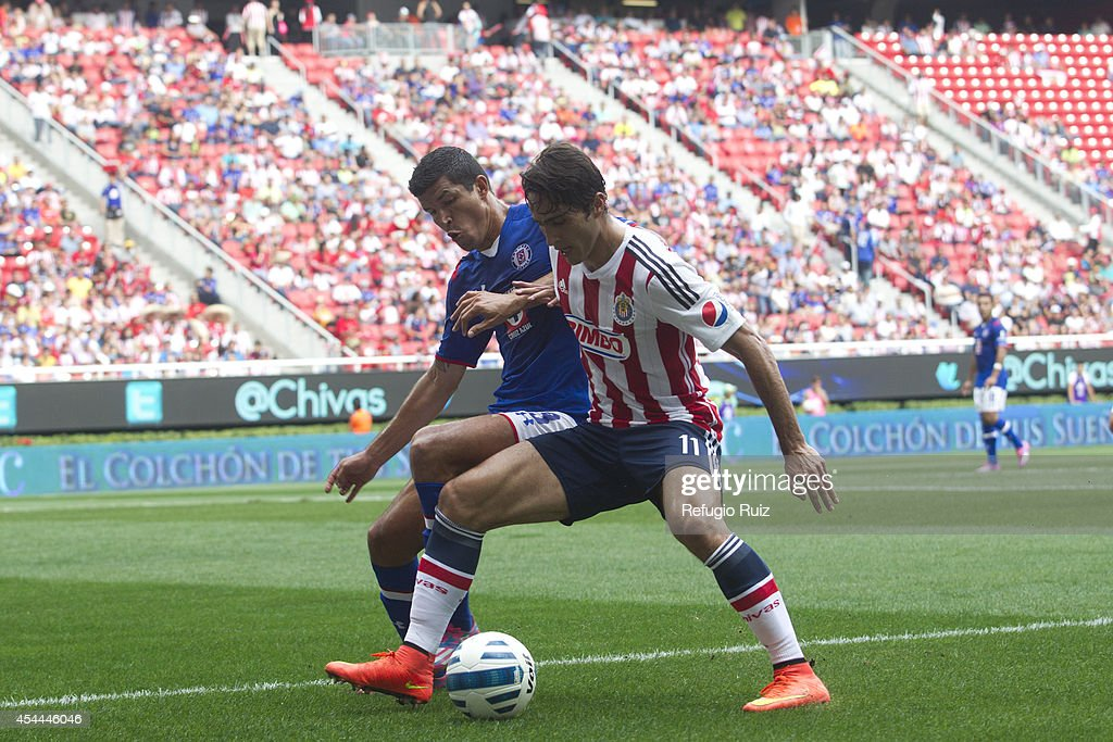 Aldo de Nigris of Chivas fights for the ball with Francisco Rodriguez of Cruz Azul during a match between Chivas and Cruz Azul a as part of Apertura 2014 Liga MX at Omnilife Stadium on August 31, 2014 in Guadalajara, Mexico.