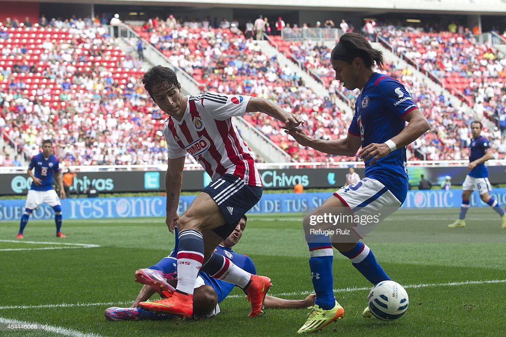 Aldo de Nigris of Chivas is dribbled by Gerardo Flores of Cruz Azul during a match between Chivas and Cruz Azul a as part of Apertura 2014 Liga MX at Omnilife Stadium on August 31, 2014 in Guadalajara, Mexico.