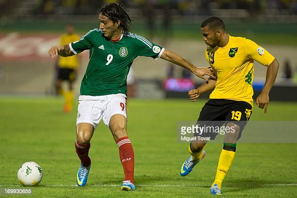 Aldo de Nigris of Mexico fights for the ball with Adrian Mariappa during a match between Mexico and Jamaica as part of the FIFA 2014 World Cup...