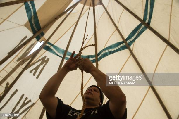 TOPSHOT Aldo Seoane a Yoeme Native American sets up a teepee near the Washington Monument in Washington DC on March 7 2017 at the start of a fourday...