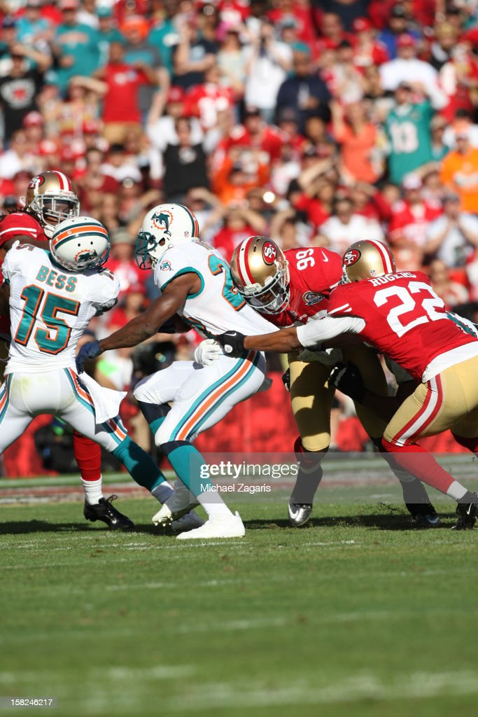 Aldon Smith #99 and Carlos Rogers #22 of the San Francisco 49ers tackle Reggie Bush #22 of the Miami Dolphins during the game at Candlestick Park on December 9, 2012 in San Francisco, California. The 49ers defeated the Dolphins 27-13.