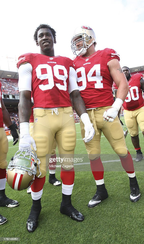 Aldon Smith #99 and Justin Smith #94 of the San Francisco 49ers stand on the field prior to the game against the Minnesota Vikings at Candlestick Park on August 25, 2013 in San Francisco, California. The 49ers defeated the Vikings 34-14.