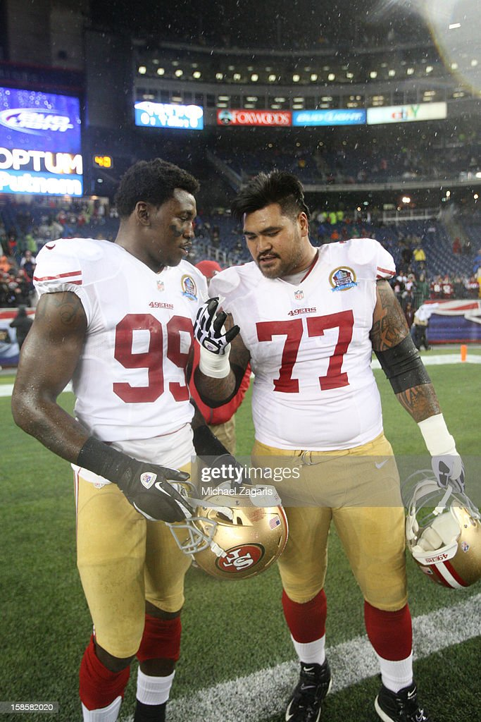 Aldon Smith #99 and Mike Iupati #77 of the San Francisco 49ers talk on the field prior to the game against the New England Patriots at Gillette Stadium on December 16, 2012 in Foxboro, Massachusetts. The 49ers defeated the Patriots 41-31.