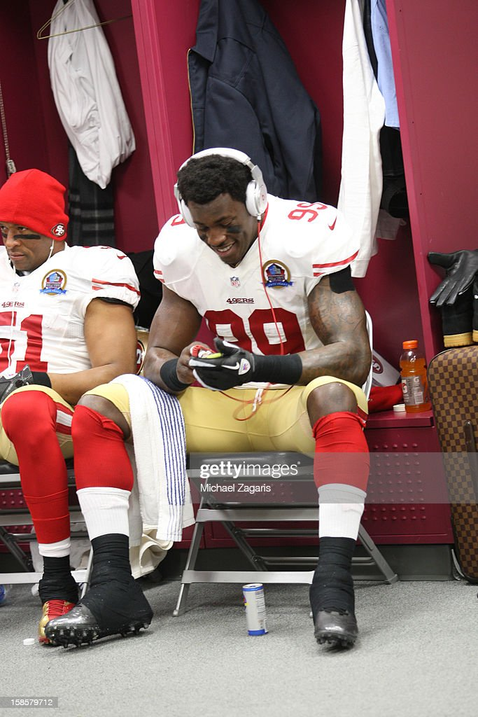 Aldon Smith #99 of the San Francisco 49ers listens to music in the locker room prior to the game against the New England Patriots at Gillette Stadium on December 16, 2012 in Foxboro, Massachusetts. The 49ers defeated the Patriots 41-31.