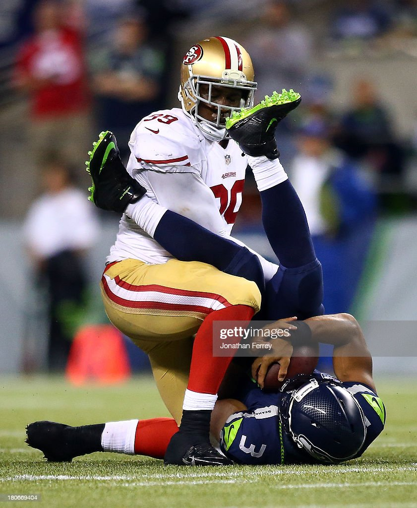Aldon Smith #99 of the San Francisco 49ers sacks Russell Wilson #3 of the Seattle Seahawks during their game at Qwest Field on September 15, 2013 in Seattle, Washington.