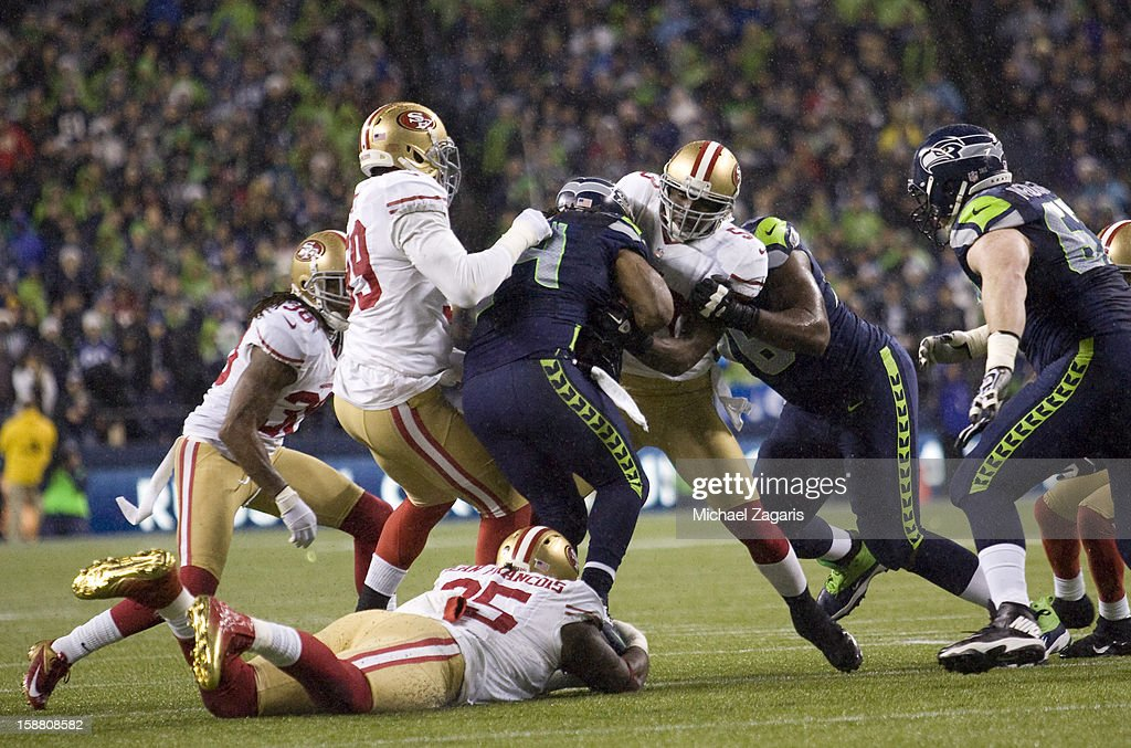 Aldon Smith #99, Ricky Jean Francois #95 and NaVorro Bowman #53 of the San Francisco 49ers tackle Marshawn Lynch #24 of the Seattle Seahawks during the game at CenturyLink Field on December 23, 2012 in Seattle, Washington. The Seahawks defeated the 49ers 42-13.