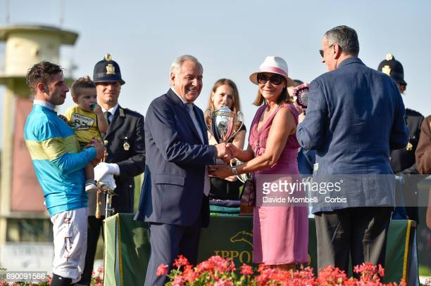 Alduino Botti accepts the trophy as jockey Nicola Pinna looks on during the prize giving ceremony for the Oaks D'Italia run at the San Siro...