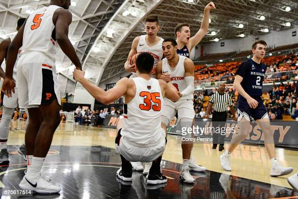 Alec Brennan of the Princeton Tigers is helped up by teammates Devin Cannady Amir Bell as Mike LeBlanc looks on as Luke Worthington of the Brigham...