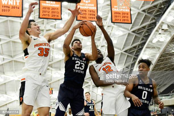 Alec Brennan of the Princeton Tigers Yoeli Childs of the Brigham Young Cougars and Myles Stephens of the Princeton Tigers battle on the boards as...