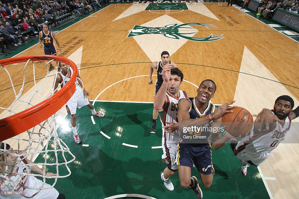 Alec Burks #10 of the Utah Jazz shoots against (L-R) Zaza Pachulia #27 and O.J. Mayo #00 of the Milwaukee Bucks on March 3, 2014 at the BMO Harris Bradley Center in Milwaukee, Wisconsin.