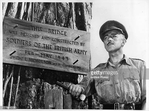 Alec Guinness in front of bridge plaque in a scene from the film 'The Bridge On The River Kwai' 1957