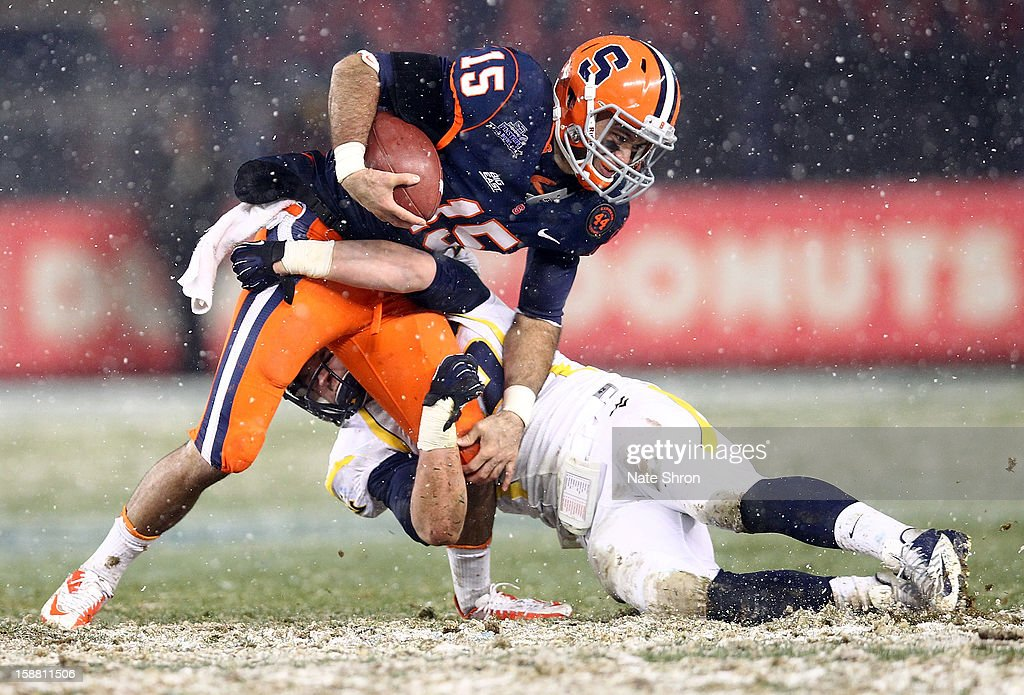 Alec Lemon #15 of the Syracuse Orange runs the ball against Nick Kwiatkoski #35 of the West Virginia Mountaineers during the New Era Pinstripe Bowl at Yankee Stadium on December 29, 2012 in the Bronx borough of New York City.