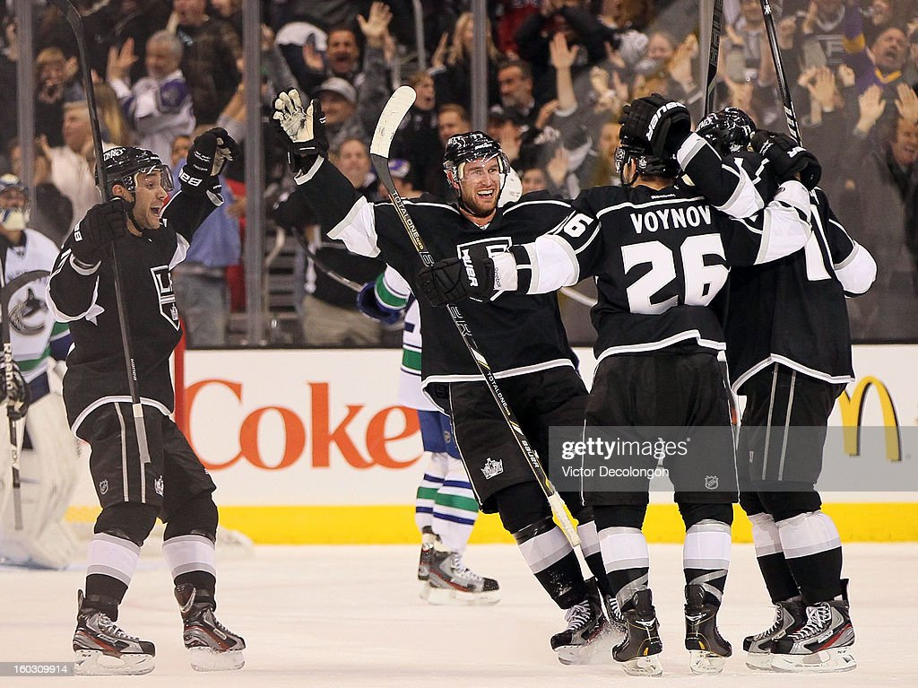 Alec Martinez #27, Jeff Carter #77, Slava Voynov #26 and Anze Kopitar #11 of the Los Angeles Kings celebrate Voynov's goal against the Vancouver Canucks in the last minute to tie the game 2-2 during the NHL game at Staples Center on January 28, 2013 in Los Angeles, California. The Kings defeated the Canucks 3-2 in shootout overtime.
