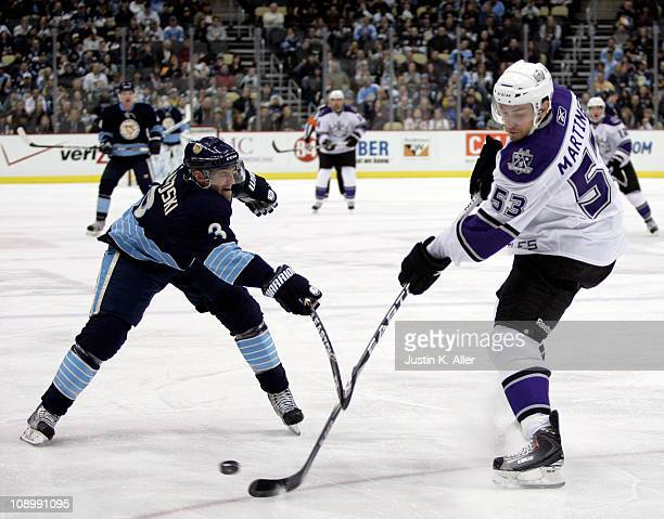 Alec Martinez of the Los Angeles Kings attempts clearing the puck past Alex Goligoski of the Pittsburgh Penguins at Consol Energy Center on February...