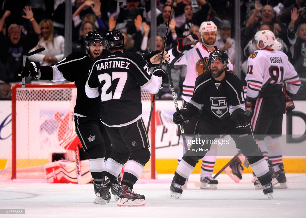 Alec Martinez #27 of the Los Angeles Kings celebrates with teammates Mike Richards #10 and Justin Williams #14 after Martinez scores a third period goal against the Chicago Blackhawks in Game Six of the Western Conference Final during the 2014 Stanley Cup Playoffs at Staples Center on May 30, 2014 in Los Angeles, California.