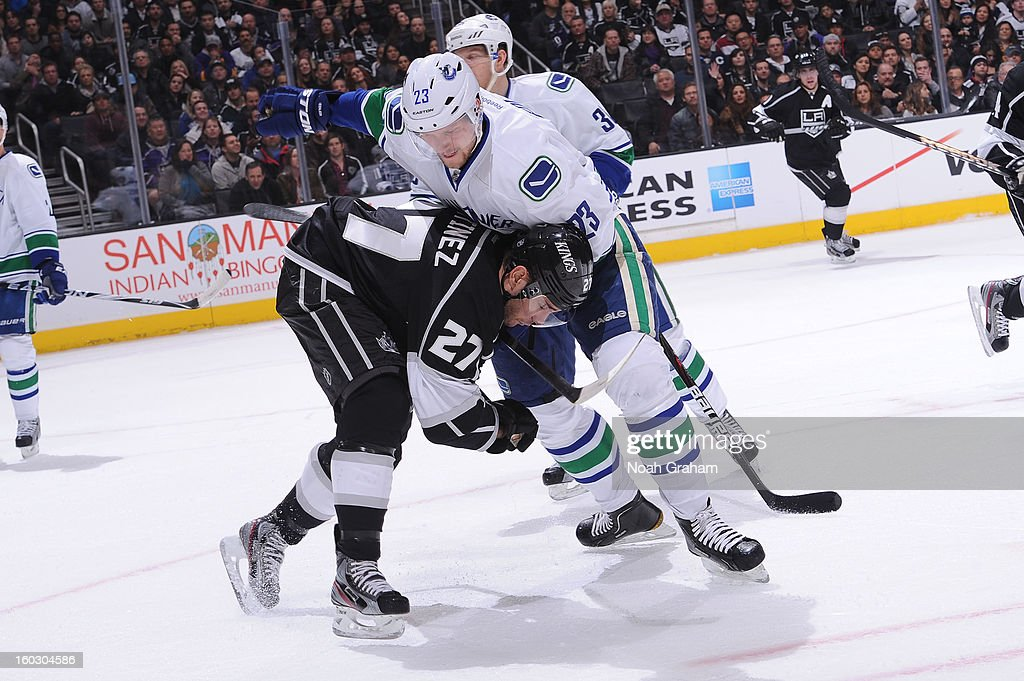 Alec Martinez #27 of the Los Angeles Kings throws the check against Alexander Edler #23 of the Vancouver Canucks at Staples Center on January 28, 2013 in Los Angeles, California.