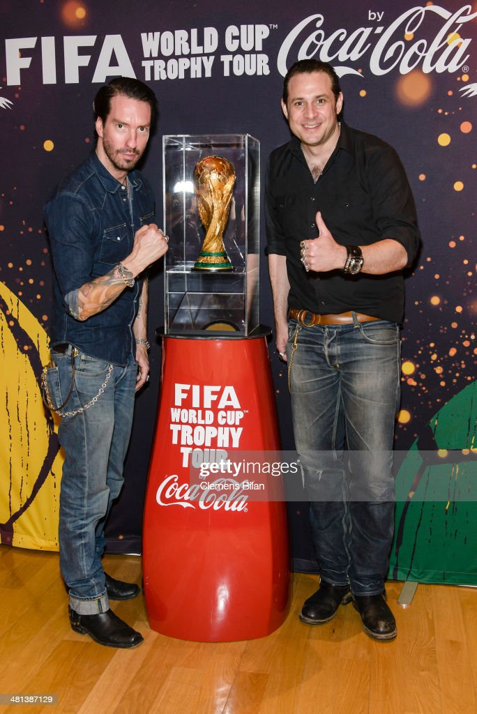 Alec Voelkl (L) and Sascha Vollmer pose with the trophy at the Gala Night of the FIFA World Cup Trophy Tour on March 29, 2014 in Berlin, Germany.