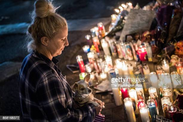 Aleca King of Las Vegas NV stops to pay tribute at vigil along Las Vegas Boulevard near Mandalay Bay hotel with her Chihuahua Falafel on Wednesday...