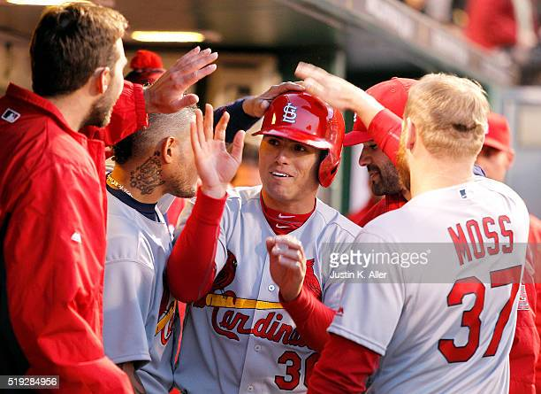 Aledmys Diaz of the St Louis Cardinals celebrates with teammates after scoring on a RBI single in the third inning during the game against the...