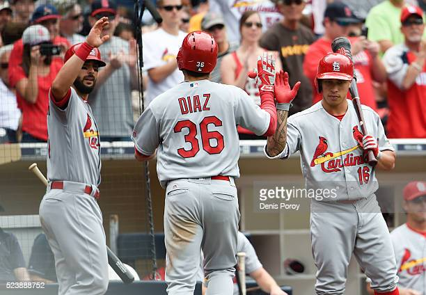 Aledmys Diaz of the St Louis Cardinals is congratulated by Matt Carpenter left and Kolten Wong after hitting a solo home run during the sixth inning...