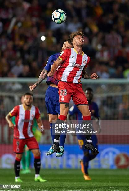 Aleix Garcia of Girona competes for the ball with Lionel Messi of Barcelona during the La Liga match between Girona and Barcelona at Municipal de...