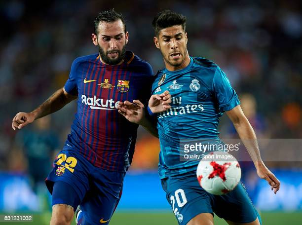 Aleix Vidal of Barcelona competes for the ball with Marco Asensio of Real Madrid during the Supercopa de Espana Supercopa Final 1st Leg match between...