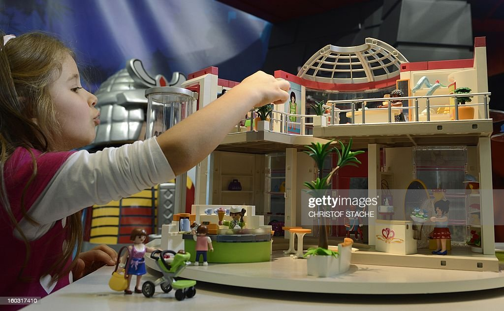 Aleja play with a Playmobil dolls house at a booth during the press preview of the international toy fair in Nuremberg, southern Germany, on January 29, 2013. Around 2.700 exhibitors show more than 1 million products at the international toy fair which opens its doors from January 29 to February 4, 2013.