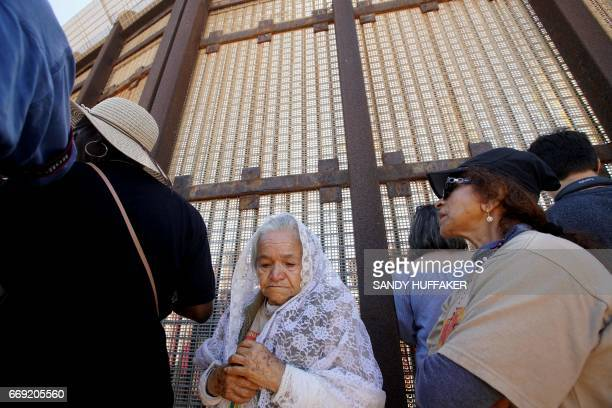 Alejandra Valles stands with other worshipers during in a binational Easter mass along the USMexico border fence at Friendship Park in San Ysidro...