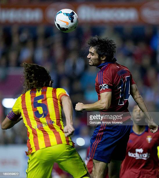 Alejandro Arribas Garrido of CA Osasuna wins the header before Carles Puyol of FC Barcelona during the La Liga match between CA Osasuna and FC...