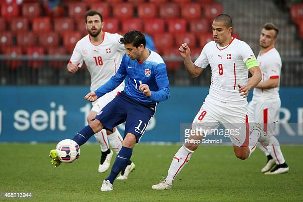 Alejandro Bedoya of the USA plays the ball under pressure from Goekhan Inler of Switzerland during the international friendly match between...