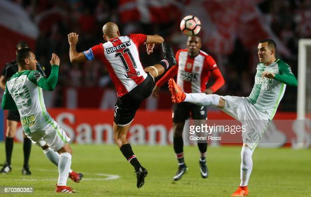 Alejandro Bernal Rios of Atletico Nacional fights for the ball with Juan Sebastian Veron of Estudiantes during a group stage match between...