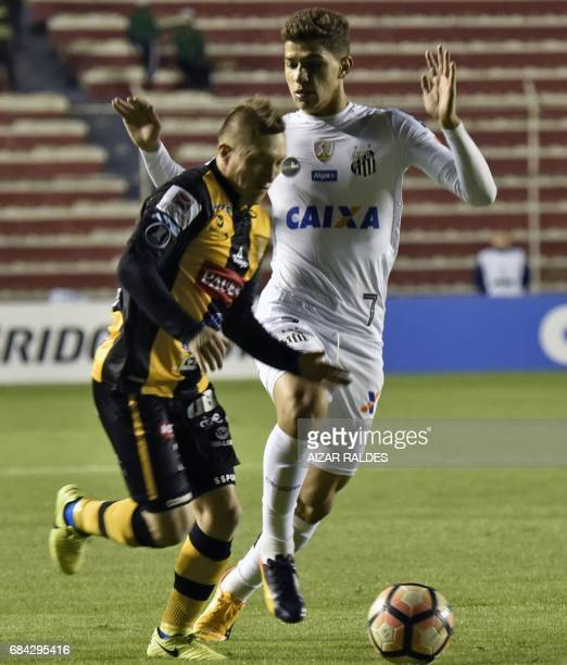 Alejandro Chumacero of Bolivia's The Strongest vies for the ball with Vitor Bueno of Brazilian Santos during a Copa Libertadores football match at...