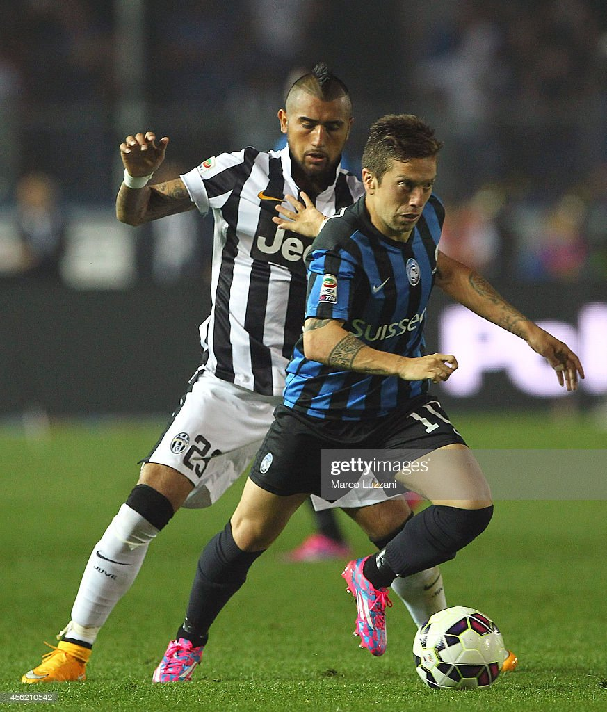 Alejandro Dario Gomez (R) of Atalanta BC competes for the ball with <a gi-track='captionPersonalityLinkClicked' href=/galleries/search?phrase=Arturo+Vidal&family=editorial&specificpeople=2223374 ng-click='$event.stopPropagation()'>Arturo Vidal</a> (L) of Juventus FC during the Serie A match between Atalanta BC v Juventus FC at Stadio Atleti Azzurri d'Italia on September 27, 2014 in Bergamo, Italy.