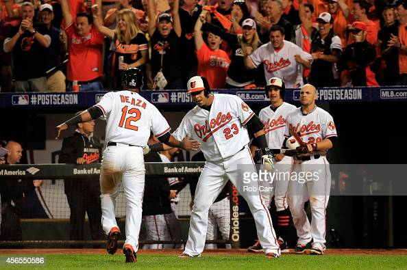 Alejandro De Aza of the Baltimore Orioles celebrates with his teammates after scoring a run in the eighth inning against the Detroit Tigers during...
