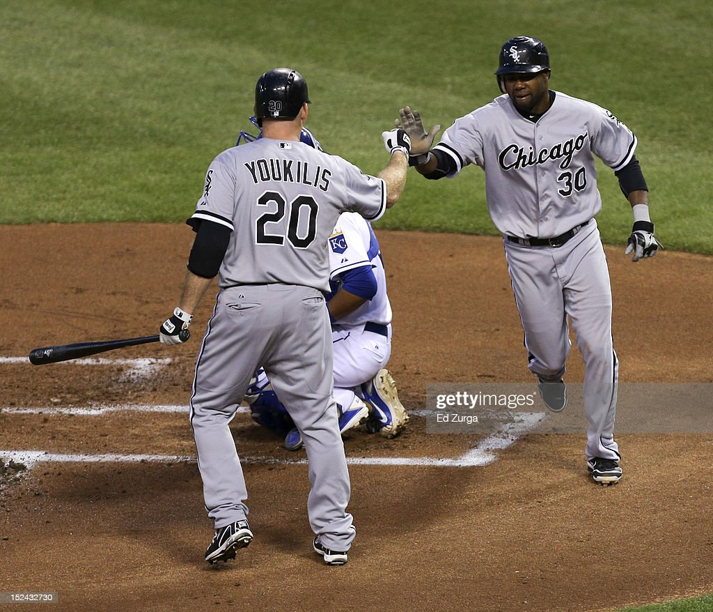 Alejandro De Aza #30 of the Chicago White Sox celebrates with Kevin Youkilis #20 as he scores on a A.J. Pierzynski single against the Kansas City Royals in the first inning at Kauffman Stadium on September 20, 2012 in Kansas City, Missouri.