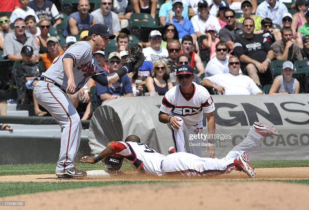 Alejandro De Aza #30 of the Chicago White Sox slides safely into third base on a sacrifice fly as Chris Johnson #23 of the Atlanta Braves makes the tag during the third inning on July 21, 2013 at U.S. Cellular Field in Chicago, Illinois.