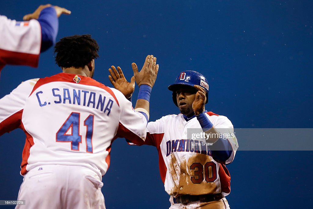 Alejandro De Aza #30 of the Dominican Republic celebrates with Carlos Santana #41 after scoring on and RBI double by Erick Aybar #2 in the fifth inning against Puerto Rico during the Championship Round of the 2013 World Baseball Classic at AT&T Park on March 19, 2013 in San Francisco, California.