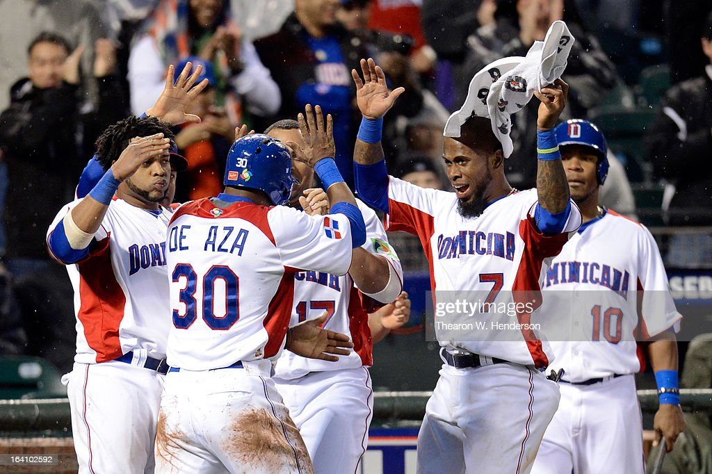 Alejandro De Aza #30 of the Dominican Republic celebrates with his team after scoring on and RBI double by Erick Aybar #2 in the fifth inning against Puerto Rico during the Championship Round of the 2013 World Baseball Classic at AT&T Park on March 19, 2013 in San Francisco, California.