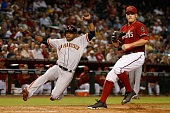 Alejandro De Aza of the San Francisco Giants scores a run past relief pitcher Andrew Chafin of the Arizona Diamondbacks on a wild pitch during the...