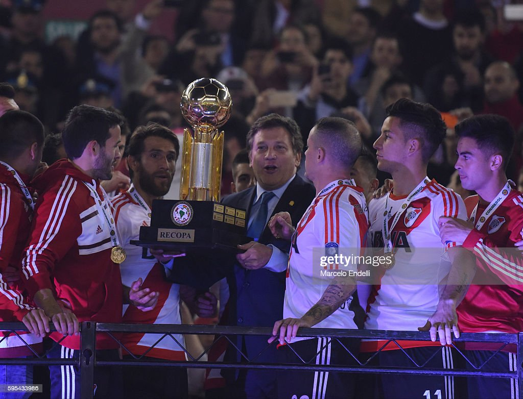 Alejandro Dominguez President of Conmebol gives the trophy to Leonardo Ponzio and Andres D'Alessandro of River Plate after a second leg match between...