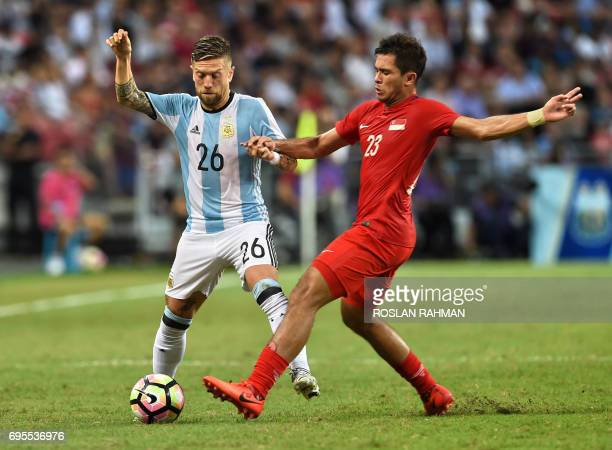 Alejandro Gomez of Argentina competes for the ball with Mohammad Shahril Bin Ishak of Singapore during their international friendly football match at...