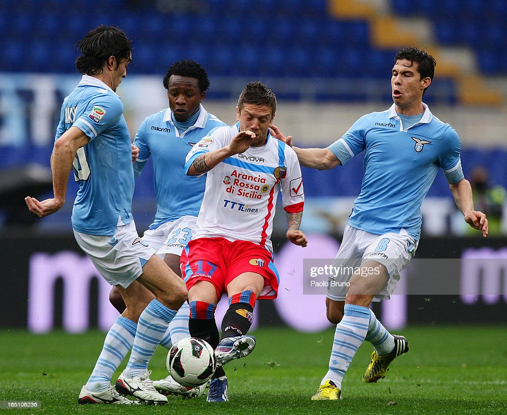 Alejandro Gomez (C) of Calcio Catania competes for the ball with S.S. Lazio players during the Serie A match between S.S. Lazio and Calcio Catania at Stadio Olimpico on March 30, 2013 in Rome, Italy.
