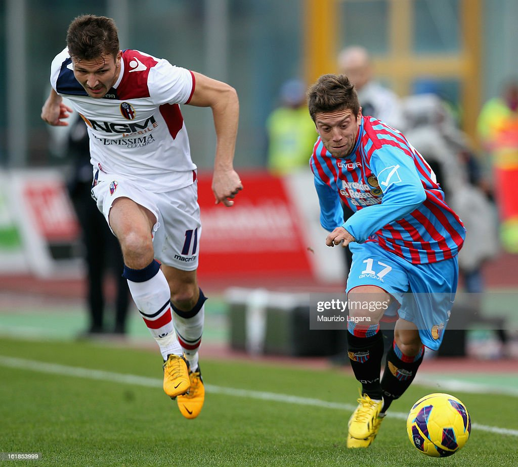 Alejandro Gomez (R) of Catania is challenged by Marco Motta of Bologna during the Serie A match between Calcio Catania and Bologna FC at Stadio Angelo Massimino on February 17, 2013 in Catania, Italy.