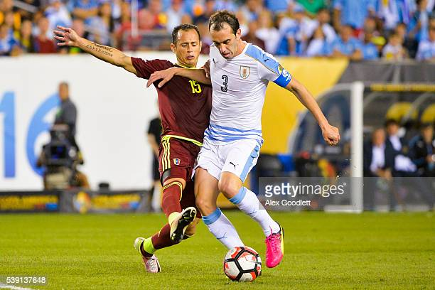 Alejandro Guerra of Venezuela fights for the ball with Diego Godin of Uruguay during a group C match between Uruguay and Venezuela at Lincoln...
