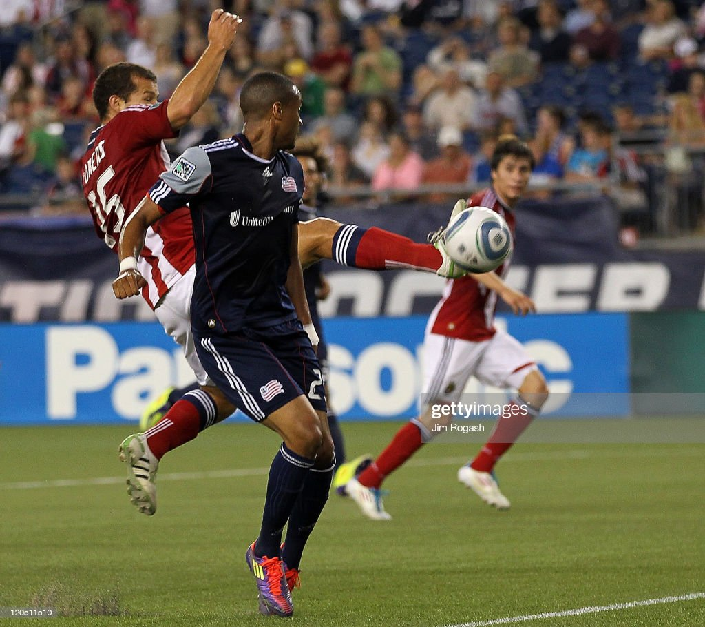 Alejandro Moreno of the Chivas USA scores by defender Darrius Barnes of the New England Revolution at Gillette Stadium on August 6 2011 in Foxboro...