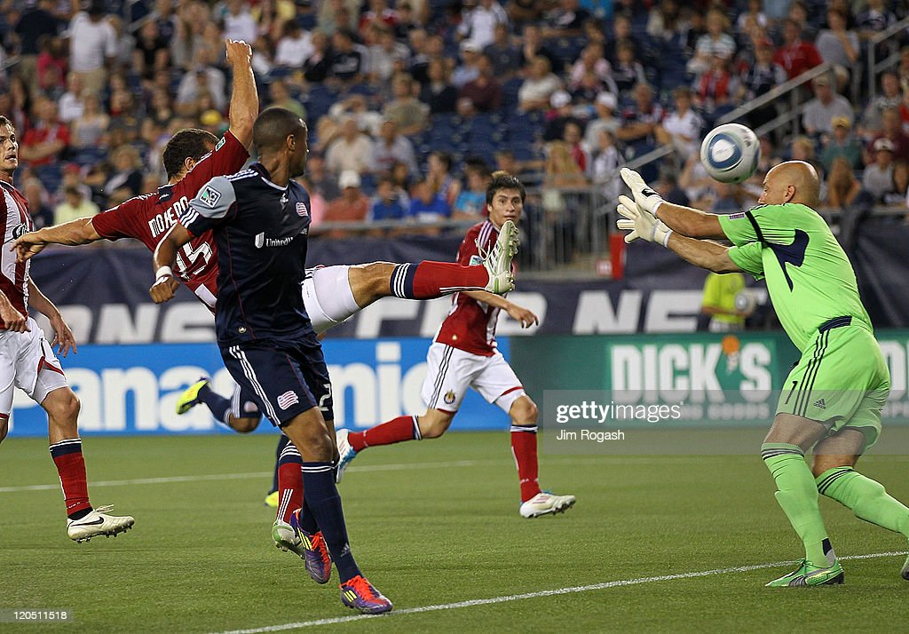 Alejandro Moreno of the Chivas USA scores by defender Darrius Barnes and Matt Reis of the New England Revolution at Gillette Stadium on August 6 2011...