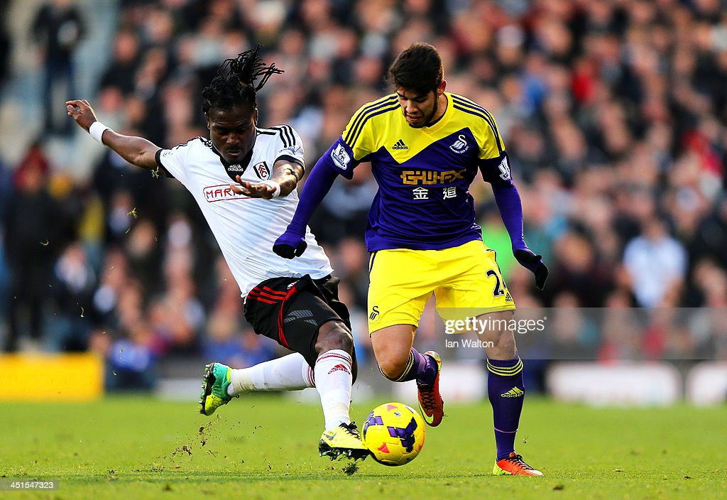 Alejandro Pozuelo of Swansea is tackled by <a gi-track='captionPersonalityLinkClicked' href=/galleries/search?phrase=Derek+Boateng&family=editorial&specificpeople=535783 ng-click='$event.stopPropagation()'>Derek Boateng</a> of Fulham during the Barclays Premier League match between Fulham and Swansea City at Craven Cottage on November 23, 2013 in London, England.