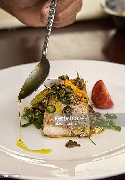 Alejandro Ruiz chef of the 'Casa Oaxaca' restaurant adds olive oil to a dorado fish dish prepared with pumpkin flower radish and capers in his...