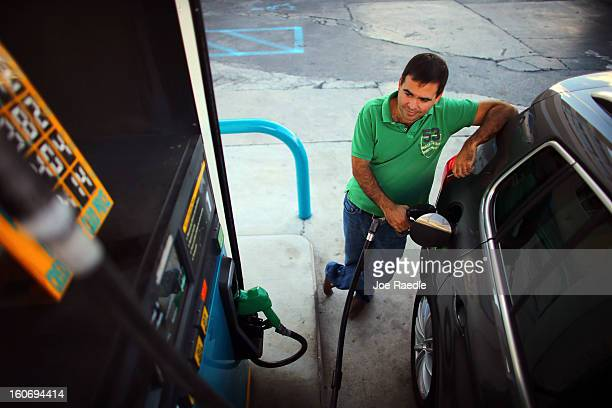 Alejandro Sanchez uses a gas station's pump to fill his vehicle with gas on February 4 2013 in Miami Florida Reports indicate that gas pump prices...